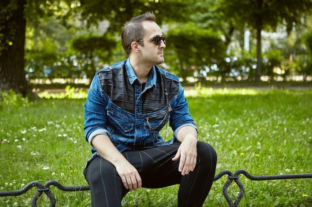 Der 27-jährige russe sitzt auf einem zaun im öffentlichen park.