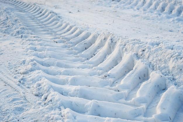 Der abdruck der lauffläche der traktorräder im schnee.