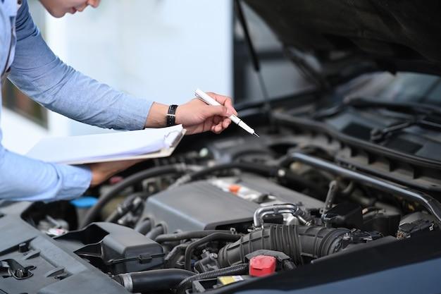 Der abgeschnittene schuss eines asiatischen männlichen autotechnikers ist eine wartung für kunden gemäß der angegebenen checkliste für die fahrzeugwartung.