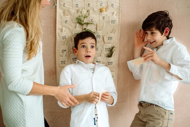 Der adventskalender hängt an der wand. geschenke überraschungen für kinder. zwei emotionale jungs