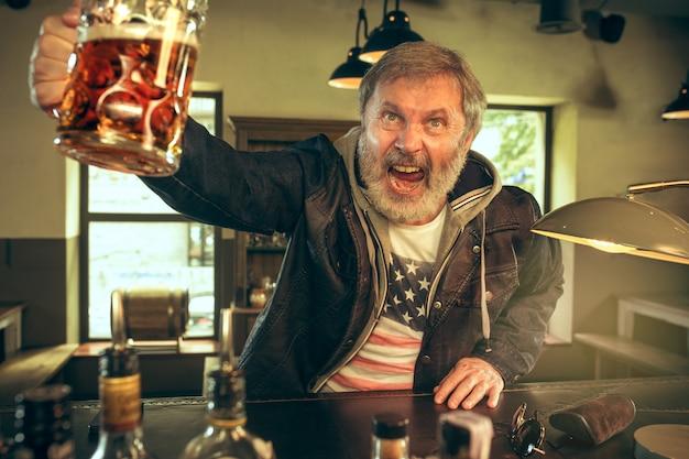Der ältere bärtige mann trinkt bier in der kneipe