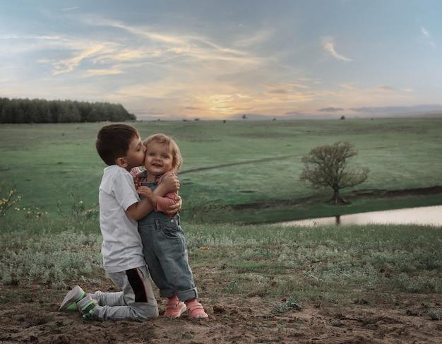 Der ältere bruder küsst seine kleine schwester vor der kulisse einer malerischen landschaft. Premium Fotos