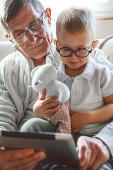 Der ältere großvater und sein kleiner enkel benutzen ein tablet