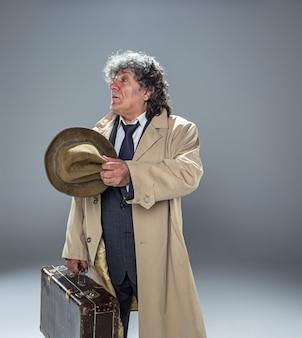 Der ältere mann als detektiv oder chef der mafia auf grauem atelier