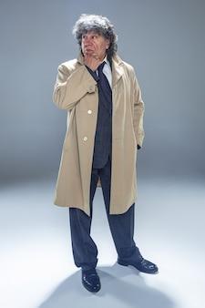 Der ältere mann als detektiv oder chef der mafia auf grauem studiohintergrund