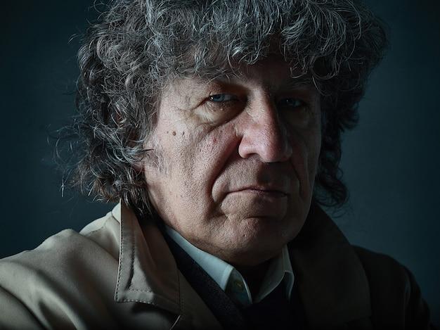 Der ältere mann als detektiv oder chef der mafia im grauen studio
