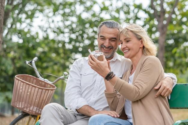 Der ältere mann des glücklichen paares überrascht, seine frau geschenkbox zu geben, während er sich entspannt und auf der bank im park sitzt
