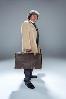 Der ältere mann im umhang als detektiv oder mafia-chef. studioaufnahme auf grau im retro-stil. reifer mann mit hut und koffer
