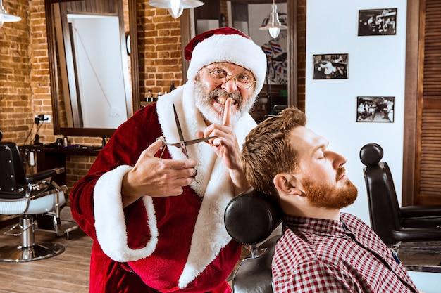 Der ältere mann im weihnachtsmannkostüm, der als persönlicher meister mit schere im friseurladen vor weihnachten arbeitet