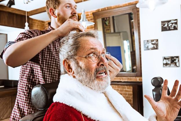 Der ältere mann im weihnachtsmannkostüm rasiert seinen persönlichen meister vor weihnachten im friseurladen