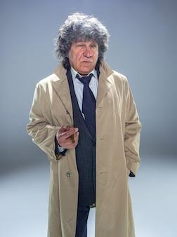 Der ältere mann mit zigarre als detektiv oder chef der mafia auf grau