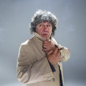Der ältere mann mit zigarre als detektiv oder chef der mafia auf grauem atelier