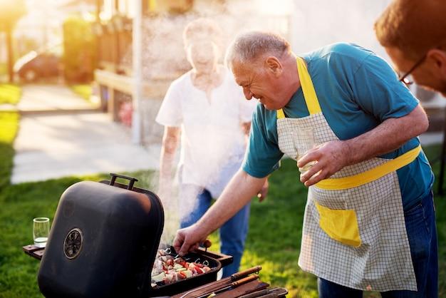Der ältere mann prüft sorgfältig, ob er fleisch vom grill nimmt, während seine frau neben ihm steht und lacht.