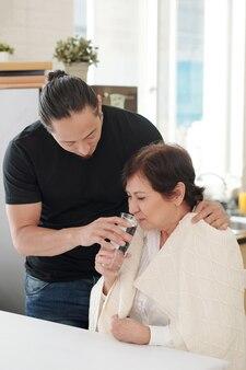 Der ältere sohn kümmert sich um seine mutter, er gibt ihr das glas wasser, während sie am tisch sitzt