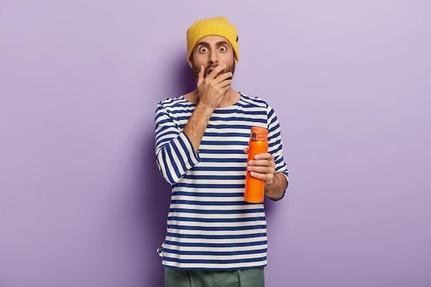 Der ängstliche, ängstliche junge tourist bedeckt den mund und starrt ihn mit verwanzten augen an