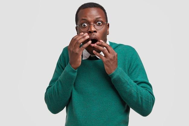 Der ängstliche afroamerikaner starrt mit verängstigtem gesichtsausdruck, als er ein großes insekt bemerkt, vor angst zittert und die hände in der nähe des mundes hält