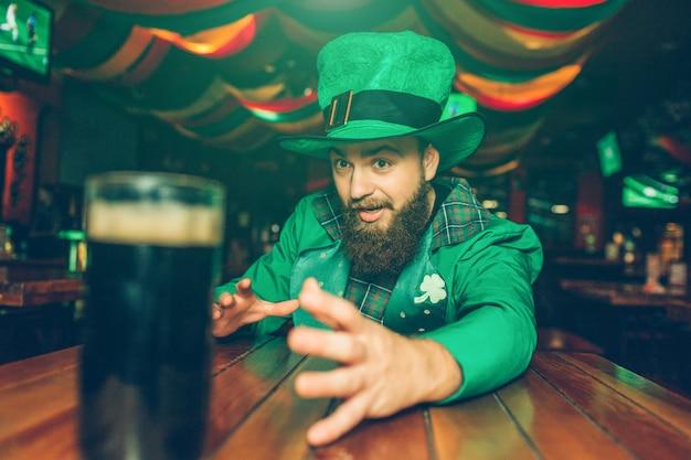 Der ängstliche bärtige kerl in der grünen klage sitzen bei tisch in der kneipe. mit der hand erreicht er einen krug dunkles bier. junger mann tragen st. patrick's anzug.