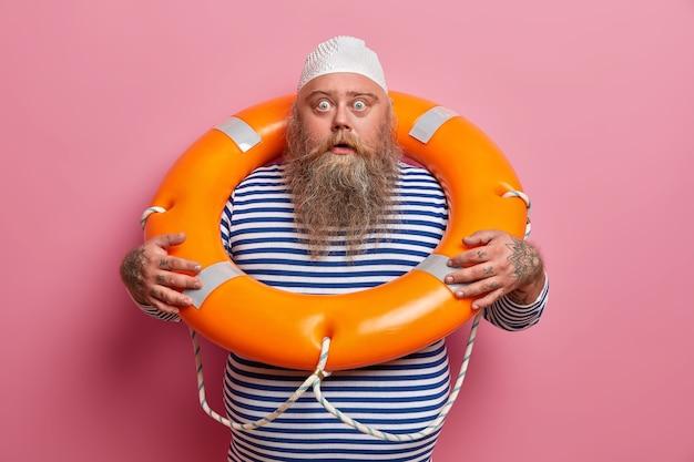 Der ängstliche emotionale bärtige mann starrt mit geschocktem blick, posiert mit lifering, trägt ein gestreiftes matrosenhemd, genießt wassererholung und sommerferien am meer, isoliert auf rosa wand