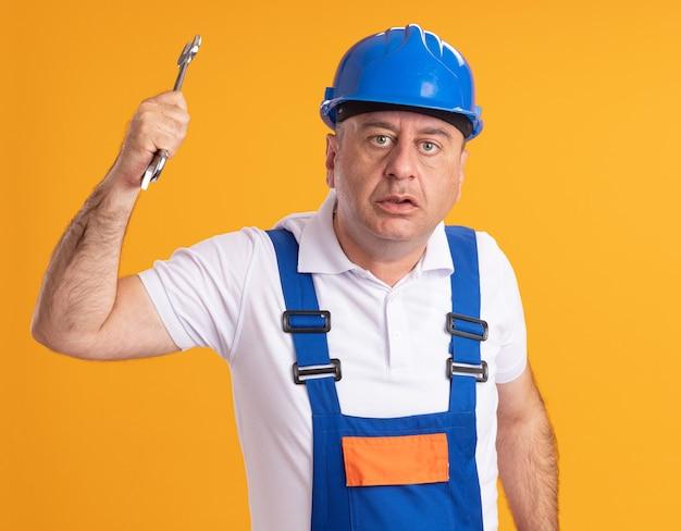 Der ängstliche erwachsene baumeister in uniform hält den schraubenschlüssel isoliert auf der orangefarbenen wand