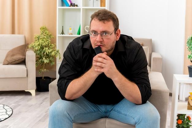 Der ängstliche erwachsene slawische mann in der optischen brille sitzt auf dem sessel und hält die fernbedienung des fernsehers nahe am mund und betrachtet die kamera im wohnzimmer