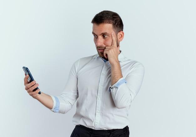 Der ängstliche gutaussehende mann legt den finger auf die schläfe, die das telefon hält und betrachtet, das auf der weißen wand lokalisiert wird
