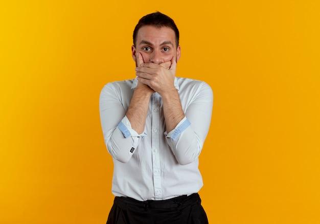 Der ängstliche gutaussehende mann schließt den mund mit den auf der orangefarbenen wand isolierten händen