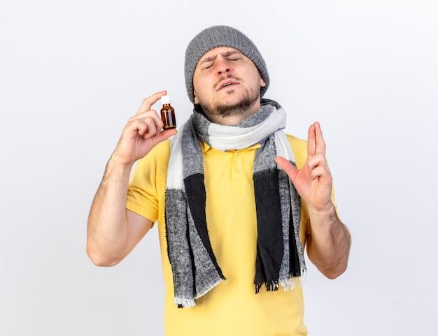 Der ängstliche junge blonde kranke mann, der wintermütze und schal trägt, kreuzt finger und hält medizin in der glasflasche lokalisiert auf weißer wand