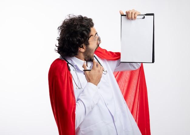 Der ängstliche junge kaukasische superheldenmann in der optischen brille, die arztuniform mit rotem umhang und mit stethoskop um den hals trägt, schaut auf zwischenablage, die bleistift lokalisiert auf weißer wand hält