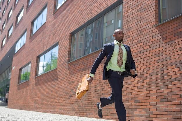 Der afrikanische mann als schwarzer geschäftsmann mit einer aktentasche, die in einer stadtstraße auf einem hintergrund der roten backsteinmauer läuft