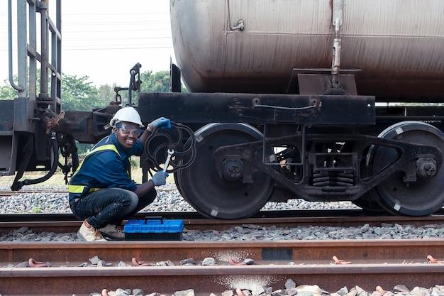 Der afrikanische maschinentechniker, der einen helm, haine und eine sicherheitsweste trägt, repariert den zug mit einem schraubenschlüssel