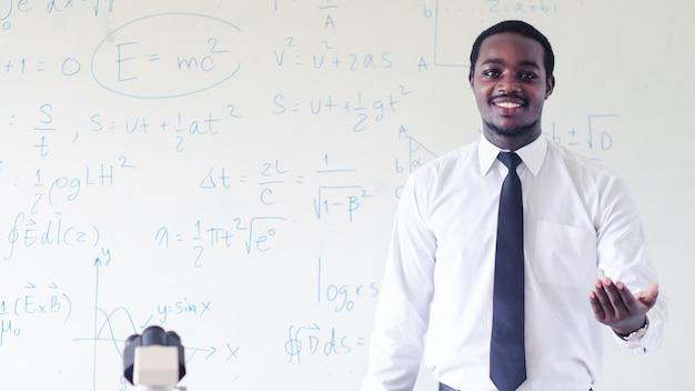 Der afrikanische wissenschaftlerlehrer unterrichtet naturwissenschaften mit mikroskop im klassenzimmer. konzept des glücklichen lehrertages