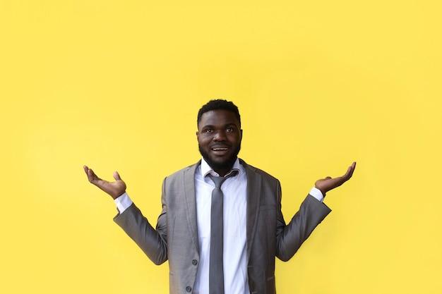 Der afroamerikaner auf gelbem grund breitet die hände aus
