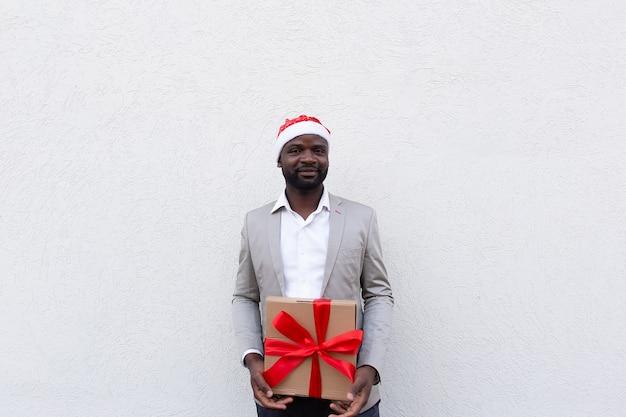 Der afroamerikaner in der neujahrsmütze mit einem geschenk