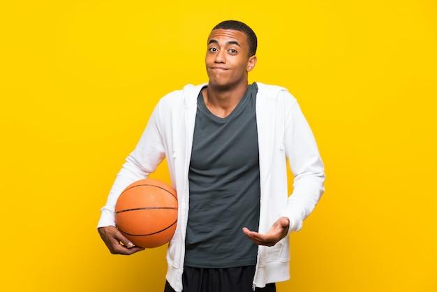 Der afroamerikanerbasketballspielermann, der zweifel macht, gestikulieren beim anheben der schultern