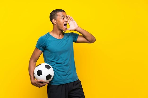 Der afroamerikanerfußballspielermann, der mit dem breiten mund schreit, öffnen sich