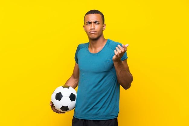 Der afroamerikanerfußballspielermann, der zweifel macht, gestikulieren beim anheben der schultern