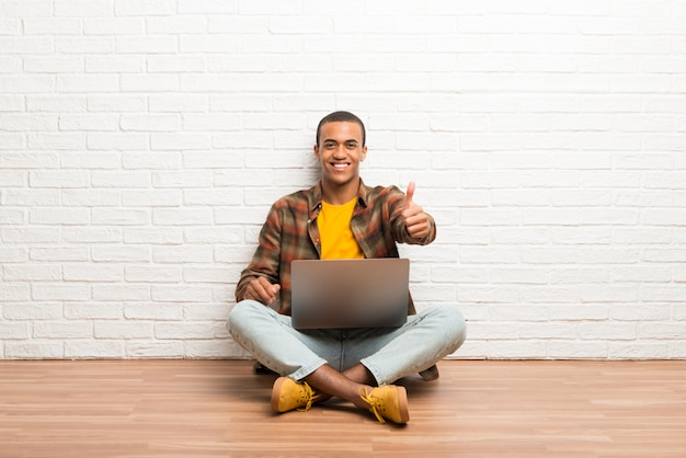 Der afroamerikanermann, der auf dem boden mit seinem laptop gibt daumen sitzt, up geste, weil etwas gutes geschehen ist