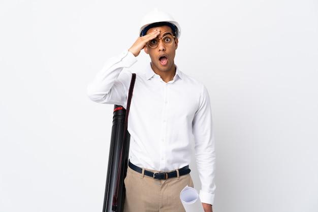 Der afroamerikanische architektenmann mit helm und blaupausen über der isolierten weißen wand hat etwas erkannt und beabsichtigt, die lösung zu finden