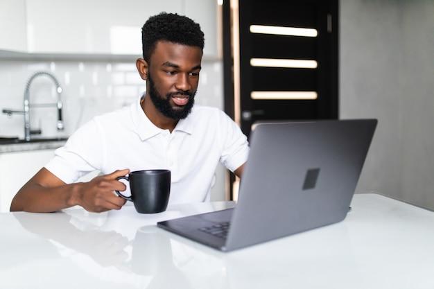 Der afroamerikanische geschäftsmann trinkt kaffee, schaut in die kamera und lächelt, während er in der küche steht