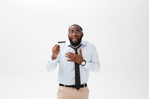 Der afroamerikanische mann, der kreditkarte über lokalisiertem hintergrund hält, erschrak im schock mit einem überraschungsgesicht