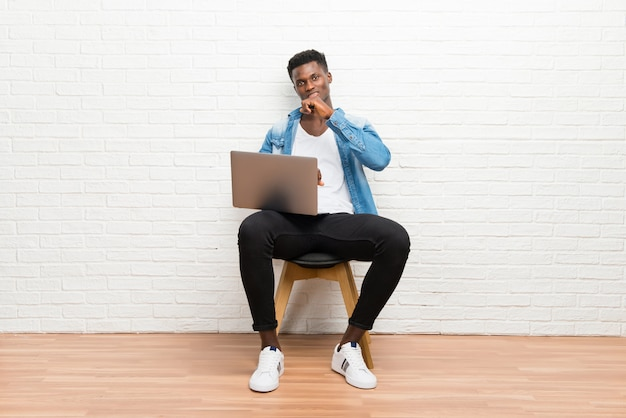 Der afroamerikanische mann, der mit seinem laptop arbeitet, leidet mit husten und fühlt sich schlecht