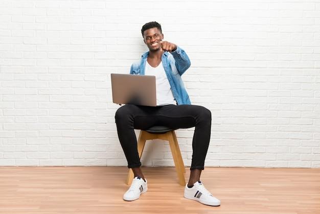 Der afroamerikanische mann, der mit seinem laptop arbeitet, zeigt finger auf sie