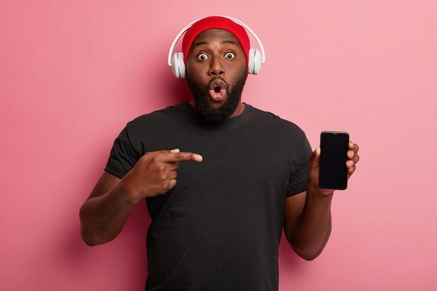 Der afroamerikanische mann zeigt auf das smartphone-display und trägt freizeitkleidung