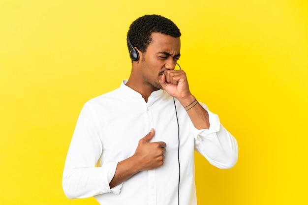 Der afroamerikanische telemarketer-mann, der mit einem headset über isoliertem gelbem hintergrund arbeitet, leidet unter husten und fühlt sich schlecht