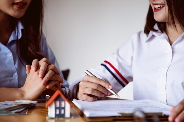 Der agent erklärt es dem kunden, bevor er einen immobilienvertrag unterzeichnet.