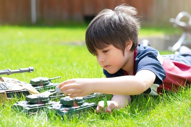 Der aktive junge, der auf dem gras spielt mit soldaten und behälter niederlegt, spielt im garten