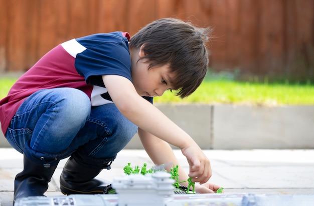 Der aktive kinderjunge, der mit soldaten und behälter spielt, spielt im garten, in der kinderphantasie und in der entwicklung