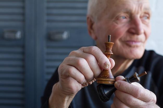 Der alte mann hält die schachfigur des königs in den händen