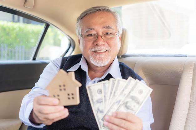 Der alte mann hält eine große anzahl von us-dollar-scheinen in einer hand, während die andere hand ein miniaturhausmodell hält, weil zuhause der zweck ist, wo er arbeitet, um geld zu verdienen - immobiliengeschäftskonzept