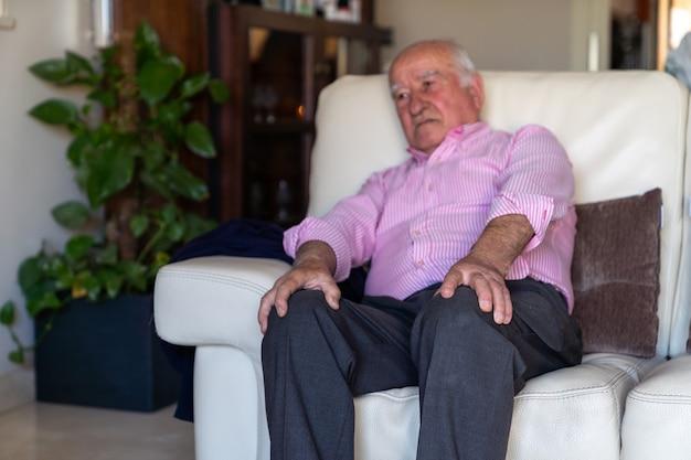 Der alte mann saß auf einem sofa und fühlte schmerzen und schmerzen auf den knien